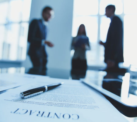 Close-up of contract with business people in the background