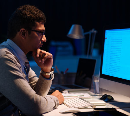 Young man working on computer at night in dark office